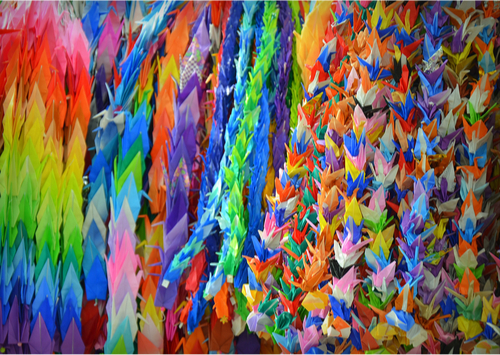 Viele bunte Origami Kraniche an Schnüren aufgereiht