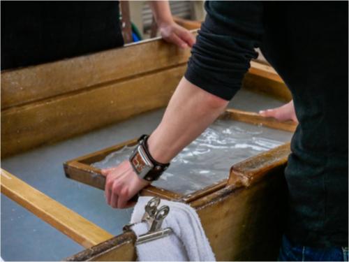 Hände halten Holzrahmen zum Papierschöpen